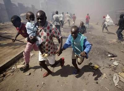 Un hombre conduce ayer a un grupo de niños fuera del suburbio de Mathare, en Nairobi, tras varios días de violencia.