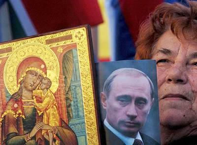 Una mujer serbia muestra un retrato del presidente ruso, Vladímir Putin, y una imagen de la Virgen María en Mitrovica durante una manifestación contra la independencia kosovar.