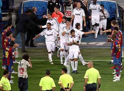 Los jugadores del Barça hacen pasillo a los del Madrid al inicio del partido.