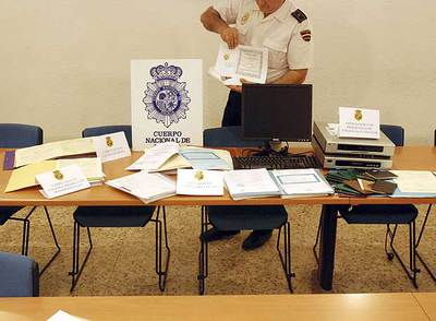 Un policía muestra parte del material incautado a la banda que tramitaba bodas falsas.