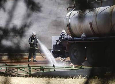 Un bombero trata de mitigar los efectos de la reacción química en la depuradora de Tres Cantos.