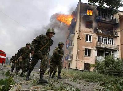 Soldados del Ejército de Georgia junto a uno de los edificios de viviendas de Gori alcanzados por la aviación rusa.