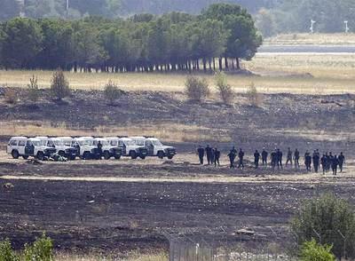 Agentes de la Guardia Civil inspeccionan el lugar del accidente del avión de Spanair junto al aeropuerto de Barajas.