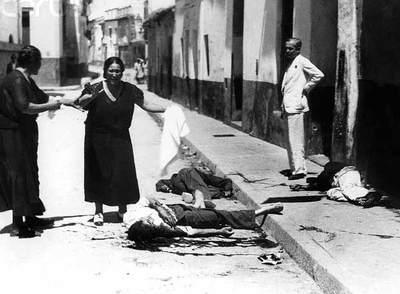 Una mujer llora ante los cadáveres de sus familiares en una calle de Sevilla, ocupada por las tropas de Franco tres días después de estallar el golpe.