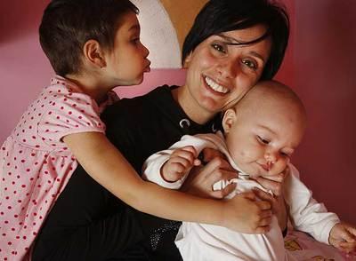 Esther González sostiene a su hija pequeña Izel mientras Erine las besa en su casa de Sant Joan de Vilatorrada (Barcelona).