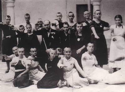 Grupo de mujeres republicanas de Montilla represaliadas por los franquistas. Se les rapó la cabeza y se les obligó a posar haciendo el saludo fascista. En el centro, el director de la banda de música, también represaliado.