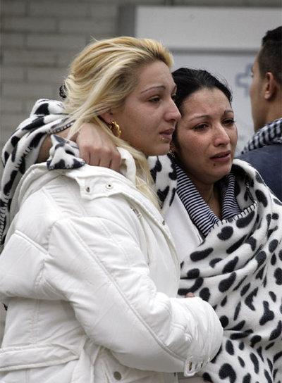 Arriba, dos mujeres esperan noticias de sus familiares en el hospital de Vall d'Hebron.