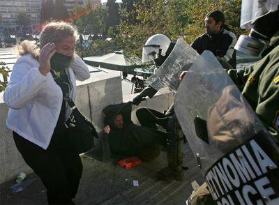 Un policía antidisturbios arremete contra un manifestante durante la protesta de ayer frente al Parlamento griego, en pleno centro de Atenas.