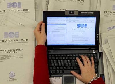Versión electrónica del BOE, rodeada de ejemplares impresos.