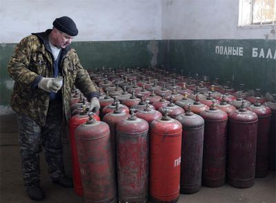 Un trabajador ucranio supervisa bombonas de gas en una estación de Brovary.