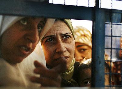 Mujeres palestinas esperan los alimentos que distribuye la ONU ante un almacén en Gaza.