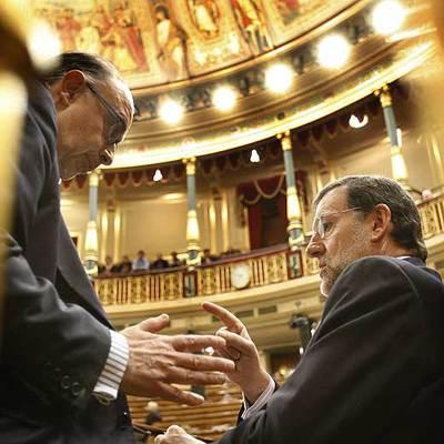 Mariano Rajoy, a la derecha, conversa en su escaño con Cristóbal Montoro en el Congreso.
