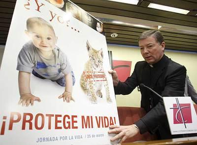 El portavoz de la Conferencia Episcopal, Juan Antonio Martínez Camino, coloca el cartel de la campaña contra el aborto.