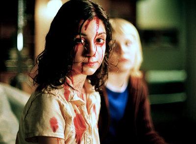 Lina Leandersson, que encarna a la niña vampiro Eli, y detrás, Kåre Hedebrant -su amigo Oskar-.