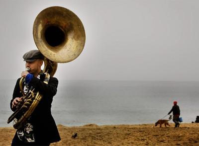Un músico sopla la tuba  en la playa de San Sebastián de la Barceloneta.