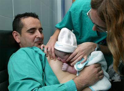 La niña ha nacido por cesárea. Mientras la madre se recupera, el padre la pone sobre su pecho. Succionar es un reflejo.