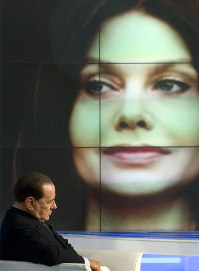 Silvio Berlusconi, con una imagen de su mujer al fondo.