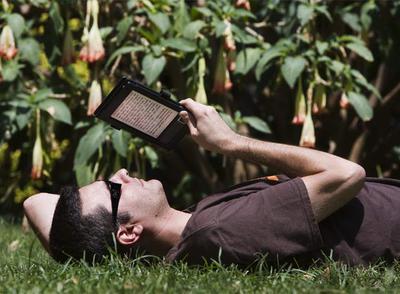Un usuario de un libro electrónico disfruta de la lectura en un parque de Barcelona.
