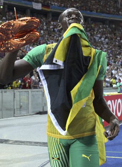 Bolt, con sus zapatillas y la bandera jamaicana.