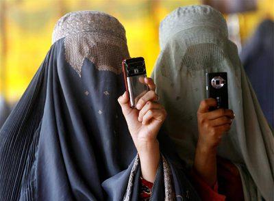 Dos mujeres ataviadas con el  burka  hacen fotos con sus móviles durante un mitin de Hamid Karzai en Kandahar.rnMujeres afganas se disponen a votar el 20 de agosto pasado.