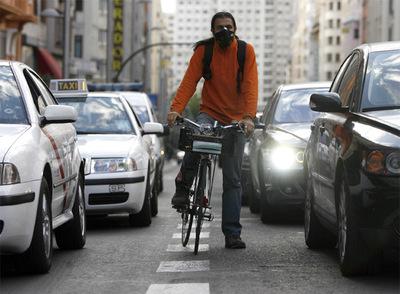Un ciclista en la Gran Vía se tapa la boca con una mascarilla para no aspirar el humo de los coches.