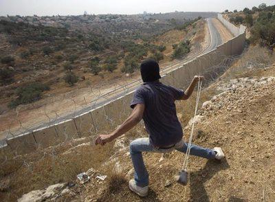 Un palestino lanza una piedra contra una patrulla israelí al otro lado del muro, cerca de Ramala.
