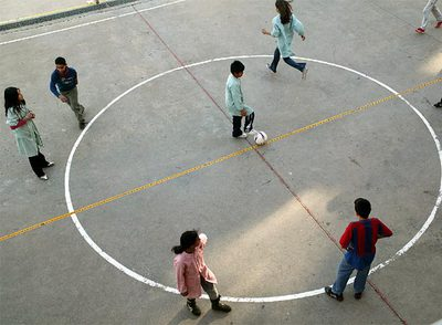 Niños jugando a fútbol en el patio del colegio Pompeu Fabra de Reus.
