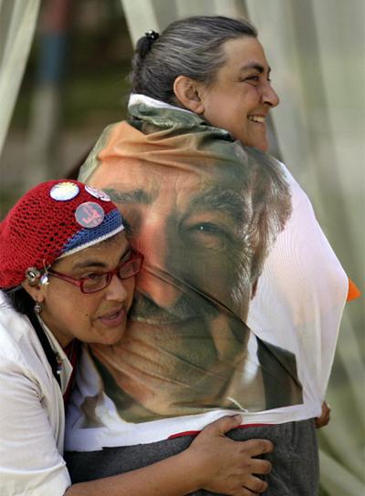 Dos mujeres celebran la victoria de Mujica con una bandera con su foto.