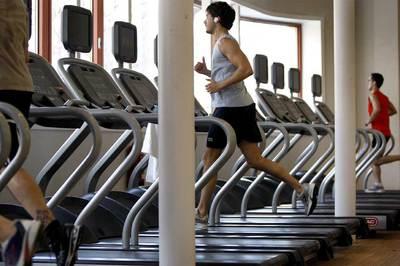 Cliente de un gimnasio escucha música mientras corre en la cinta.