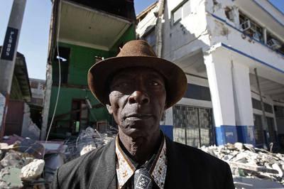 Un haitiano delante de edificios destruidos