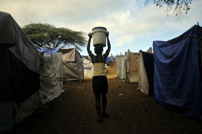 Una mujer haitiana carga un bidón de agua en un campamento levantado en un club de golf de Puerto Príncipe.