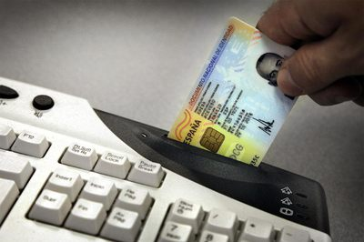 Un usuario introduce su DNI-e en el lector de la tarjeta para acceder a las operaciones.