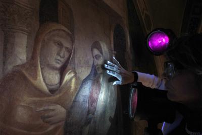 Un restaurador utiliza luz ultravioleta para ver con detalle las pinturas de Giotto en la capilla Peruzzi de la basílica florentina de la Santa Cruz.