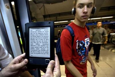 Un usuario sostiene un libro electrónico en el metro de Barcelona.