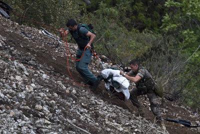 Dos militares españoles trasladan uno de los cadáveres.