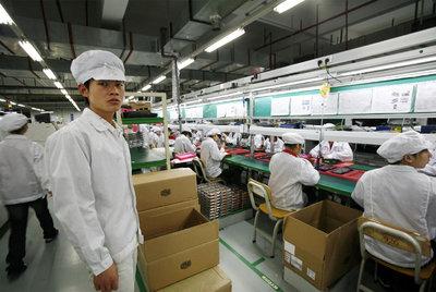 Arriba, trabajadores en la fábrica de Foxconn.