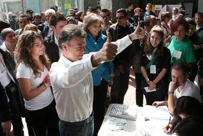 El candidato oficialista Juan Manuel Santos, ganador de la primera vuelta, hace el signo de la victoria tras depositar su voto en Bogotá.