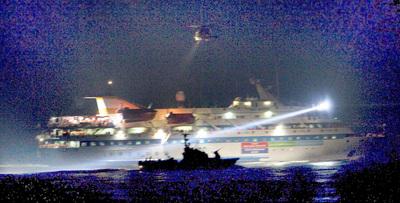 La silueta de una patrullera israelí se recorta sobre uno de los barcos de la  flotilla  durante el asalto.