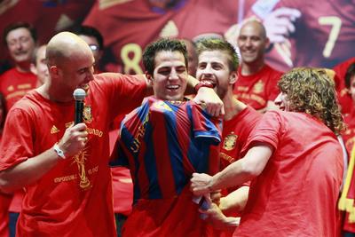 Reina, Piqué y Puyol ponen la camiseta del Barcelona a Cesc, jugador del Arsenal.