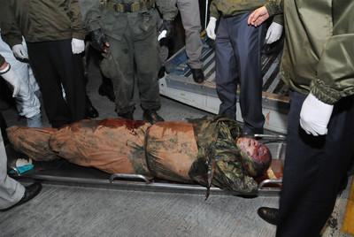 Agentes de la policía observan el cadáver del Mono Jojoy en el aeropuerto militar de Catam, en Bogotá, el jueves.