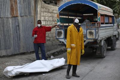 Miembros del equipo sanitario encargado de recoger cadáveres sacan varios cuerpos de un hospital de Puerto Príncipe, el pasado domingo.