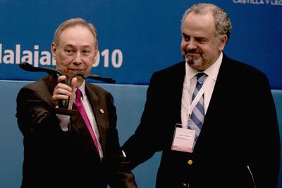 Humberto López Morales muestra el galardón que le entregó Ignacio Polanco.