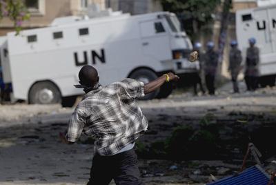 Un haitiano arroja una piedra a un vehículo de la ONU durante una protesta en Puerto Príncipe.