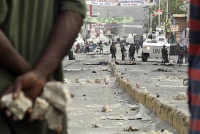 Jóvenes armados con piedras se disponen a atacar a las fuerzas de la ONU, ayer en Puerto Príncipe.