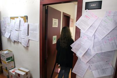 En los juzgados 31 y 32 de Madrid, especializados en hipotecas, los edictos de subastas de pisos ya no caben en el tablón de anuncios y hay que ponerlos en puertas y  paredes.