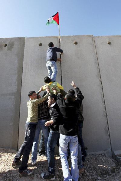 Jóvenes palestinos colocan su bandera en el muro erigido por Israel.