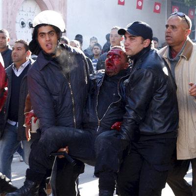 Dos policías transportan a un colega herido en una manifestación frente a la sede del Gobierno en Túnez.