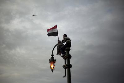 Un  manifestante, subido a una farola, protesta contra el régimen de Mubarak en la plaza Tahrir, en el centro de El Cairo. Muchos siguieron las convocatorias a través de Internet.