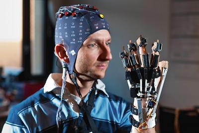 Un colaborador del profesor Millán lleva puesta la capucha de electrodos y practica para mover una mano con el pensamiento.
