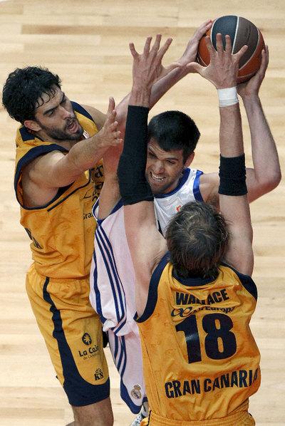 Felipe Reyes trata de eludir el marcaje de Beirán y Wallace.